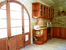 BALLUTA holiday house kitchen with door leading to pool area